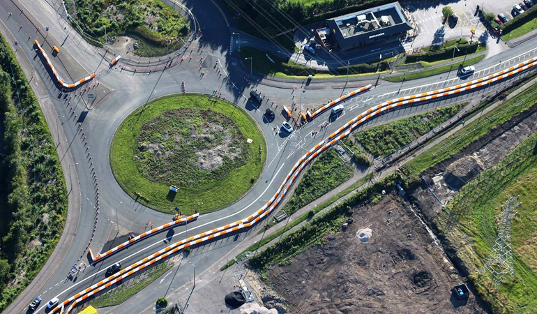 An aerial view of traffic management at a roundabout to create a safe working area