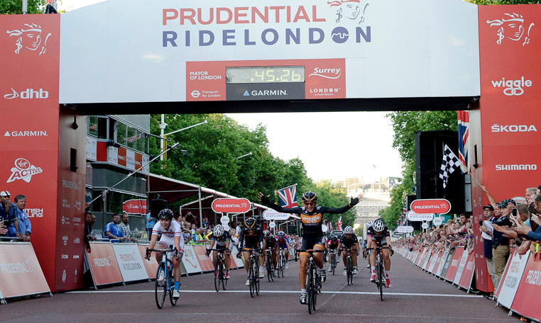 Competitors cfrross the finish line at the Prudential Ride London Event while spctators enjoy the action from behind crowd control barriers