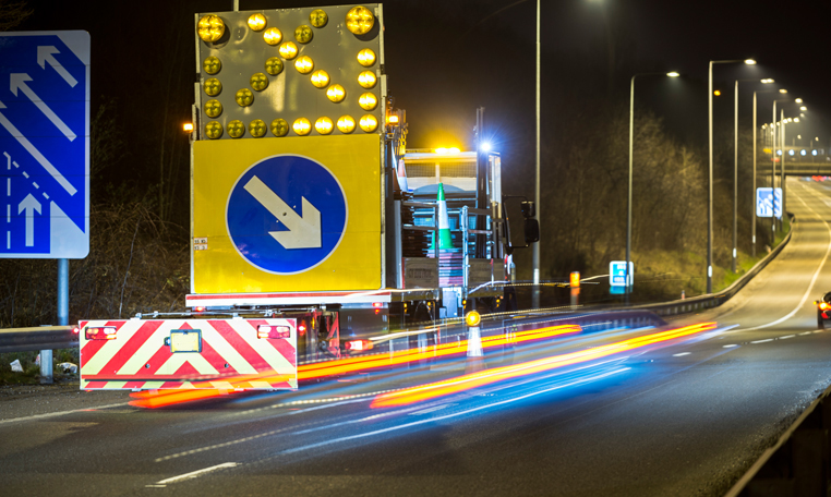A well lit traffic management vehicle diverts traffic at night