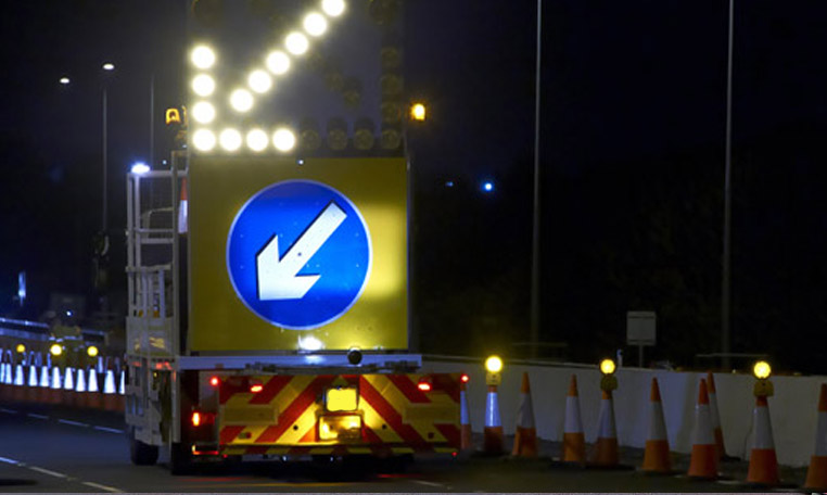 Roadworks operatives and members of the public are kept safe at night by using a traffic management system that includes a coned off are with lights and an impact prevention vehicle to divert traffic