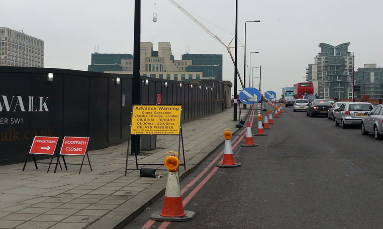 Cones & Signage are used to close a lane of traffic over a bridge, pedestrian management is also used to prevent people from entering the work area
