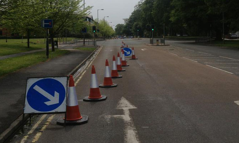 Cones & Signs are used to close a lane of a highway heading up to traffic lights